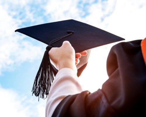 Graduate holding cap